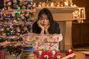 Stressed lady wrapping gifts with Christmas tree in background