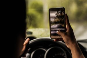 Man taking picture with cell phone while driving